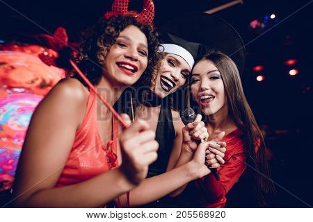 Halloween party. Three girls in sexy outfits kinoshnyh villains are posing in a nightclub. They sing in karaoke and have fun