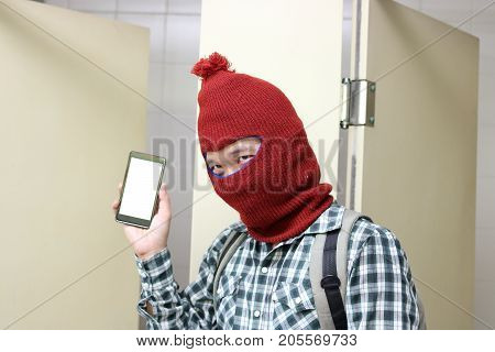 Masked bruglar holding and showing mobile smart phone on his hands in toilet. Dangerous social crime concept.