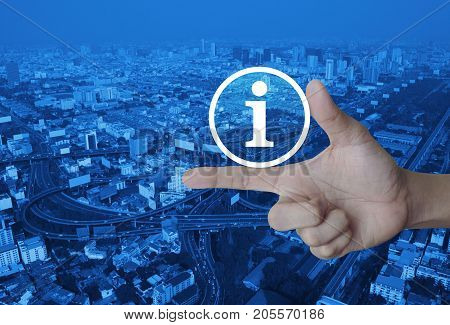 Information sign icon on finger over modern city tower street and expressway Business communication concept