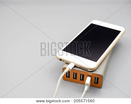 Smart phone charging with multiport USB power adaptor on gray background with copy space Selective focus