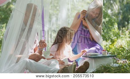 Portrait of cute blonde little girl with family in park, view