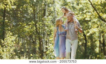 Father - bold man, mother - blonde beautiful woman and little girl - walking in the park at sunny day, telephoto
