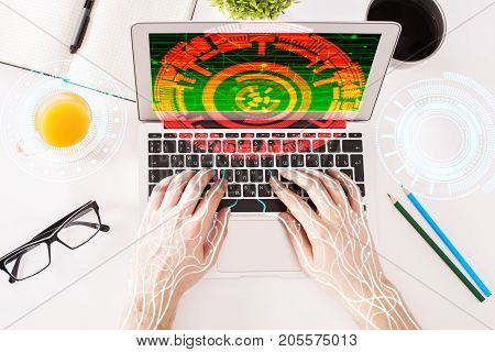 Top view of abstract cyborg circuit hands using laptop with digital button placed on white office desktop with supplies and other items. Future concept