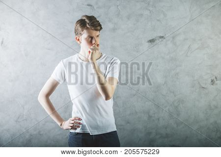 Portrait of pondering young businessman on textured concrete wall background