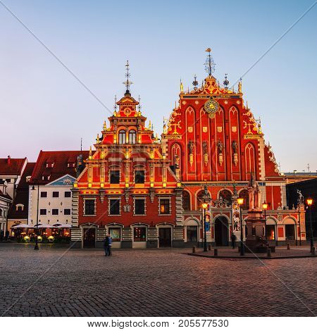 Illuminated House of the Blackheads in the old town of Riga, Latvia. Unidentified blurred people walking by the square at sunset