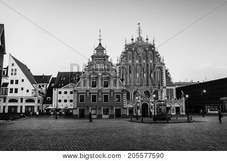 Riga, Latvia. Illuminated House of the Blackheads in the old town of Riga, Latvia. Unidentified blurred people walking by the square at sunset. Black and white