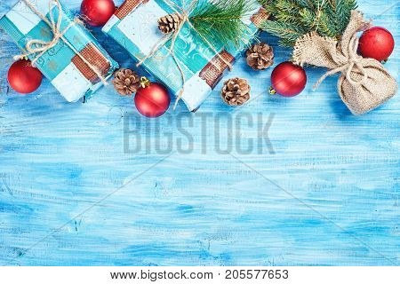 Top view of Christmas background on blue wooden board with fir red decorations cones and gift boxes forming top rim. Copy space.
