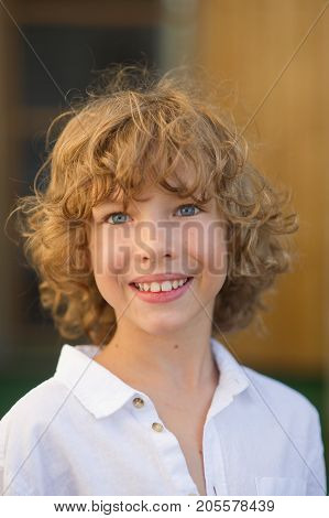 Portrait of the nice boy of 10-11 years. The fellow has beautiful fair curly hair blue cheerful eyes suntanned skin a pleasant smile. The boy is dressed in a white shirt.