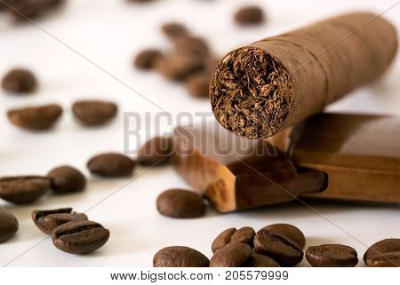 Cigar with coffee beans and lighter closeup