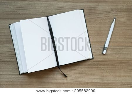 topview of notebook with blank pages and pen on desk