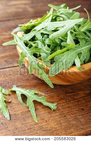 Fresh arugula on a wooden background agricultural product organic product space for text