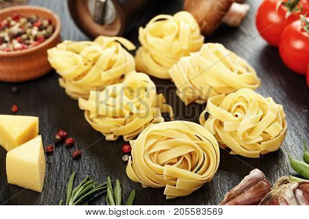 raw tagliatelle with vegetables - with cherry tomatoes cheese and spices on a black background