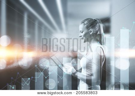 Side view of attractive woman using tablet on creative night city background with business chart. Technology and financial growth concept. Double exposure