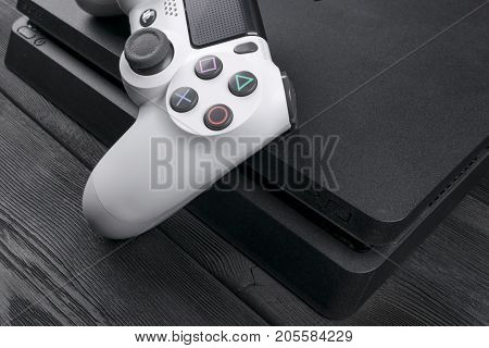 Sankt-Petersburg Russia September 24 2017: Sony PlayStation 4 Slim 1Tb revision and dualshock game controller. Game console with a joystick. Home video game console on wood background