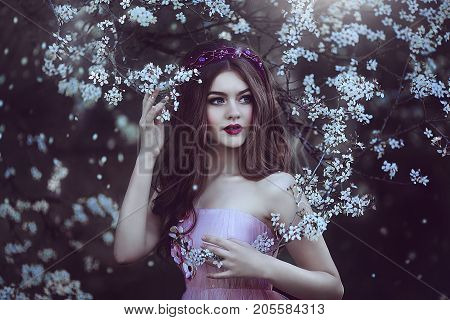 Beautiful Romantic Girl with long hair in pink dress near flowering tree.Fantasy art. Creative colors and Artistic processing.