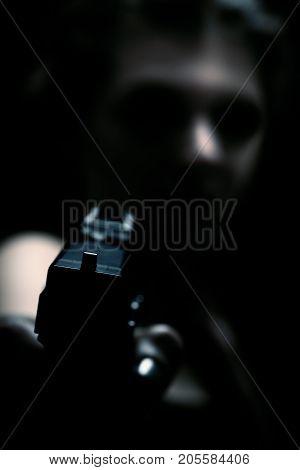 beautiful young woman with gun in dark aiming at camera, blurred image