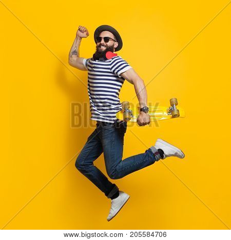 Side view of stylish hipster man with cruiser board jumping on colorful yellow background.