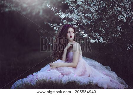 Beautiful Romantic Girl with long hair in fairy long pink dress sitting near flowering tree.Fantasy art. Creative colors and Artistic processing.