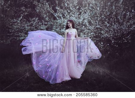 Beautiful Romantic Girl with long hair in fairy long pink dress standing near flowering tree.Fantasy art. Creative colors and Artistic processing.
