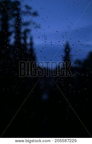 view through window with raindrops on a gloomy rainy day. focus on rain drops.