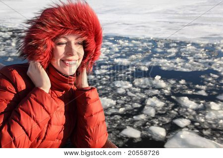 beautiful young woman in red jacket, smiling and standing near river at winter