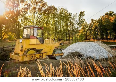 Yellow old machine for laying asphalt on the road in the morning at dawn near the heap of gravel .