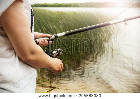 female hands holding a fishing rod and twist the handle of the fishing reel. Shallow depth of field, soft focus