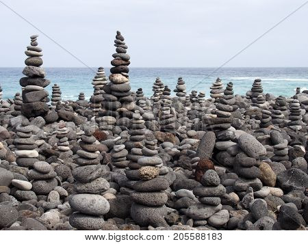 pebbles and stones arranged into many tall stacked shapes in shades of grey on a beach