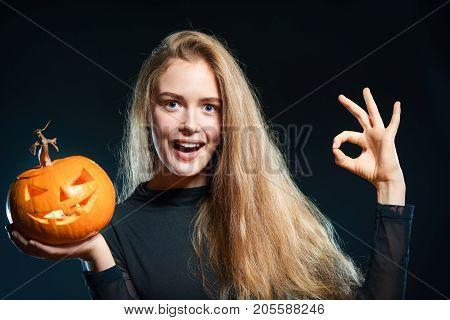 Closeup of happy woman with Halloween pumpkin gesturing OK sign over dark background