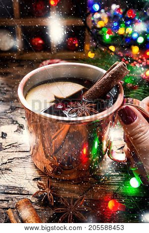 Mulled wine in copper mug with christmas decorations on wooden table