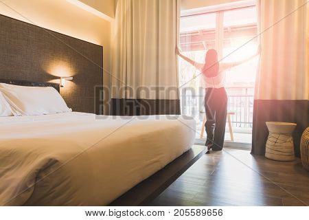 Asian women are staying in a hotel room. Open the curtain in the room looking to outside view.Vintage tone.