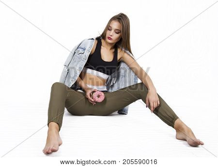 passionate young woman holding a donut between her legs. provocation concept. on a white background
