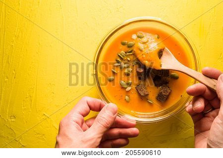 Pumpkin soup with seeds and croutons on a yellow table and spoon in hand horizontal