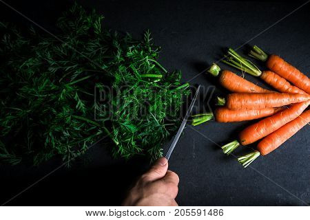 Sliced tops of carrots, carrots and and a knife in hand horizontal
