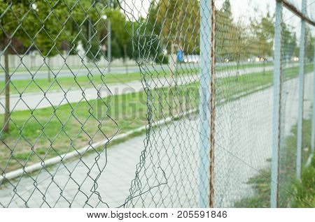 Chain link wire fence with hole in the line with street