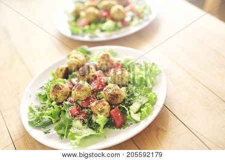 Fried falafel in a cast-iron pan close up. Middle eastern dish falafel pan and dishes with salad on the wooden background