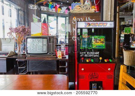 BANGKOK THAILAND - MAY 1 : red vintage arcade machine with retro television in a room on May 1 2017 in Bangkok Thailand.