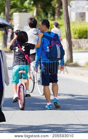 OSAKA JAPAN - SEPTEMBER 18 : unidentified asian little girl riding a unicycle (one wheel bike) with her father in a park on September 18 2017 in Osaka Japan.