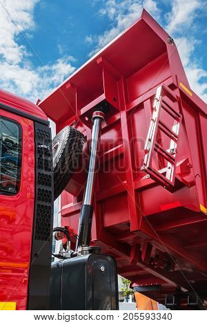 raised body red dump truck to remove soil