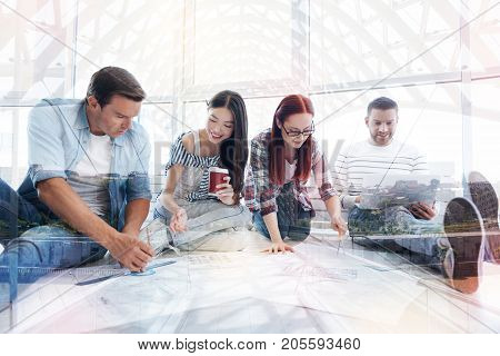 Doing tasks. Group of concentrated colleagues working attentively while sitting on the floor and showing concern