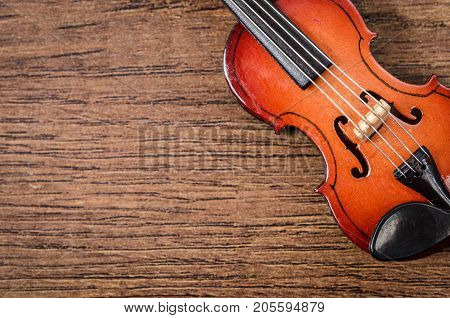 Art. Closeup of old wooden violin stringed instrument on old wooden table.