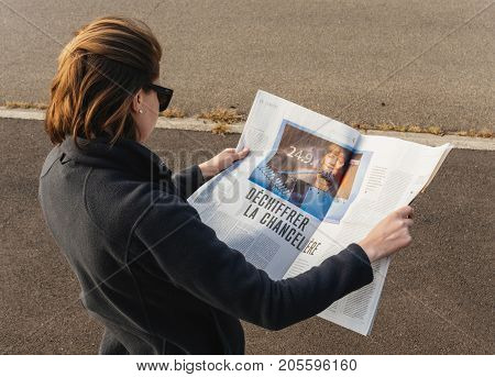 PARIS FRANCE - SEP 24 2017: Side view of woman reading latest newspaper Le Monde with article investigation about Angela Merkel before the election in Germany for the Chancellor of Germany the head of the federal government