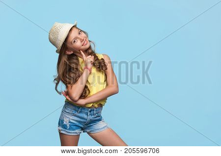 Adorable little girl in summer outfit and straw hat posing cheerfully on blue background.