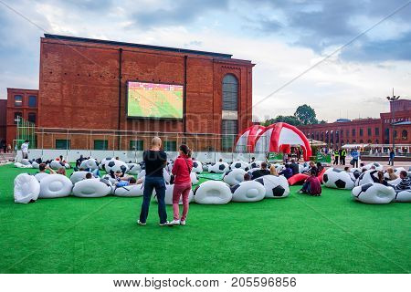 LODZ, POLAND - JUNE, 2012: Football fans watching match outdoors on confortable bean bags Euro 2012