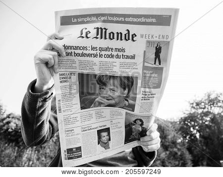 PARIS FRANCE - SEP 24 2017: View from below of woman reading latest newspaper Le Monde with portrait of Angela Merkel before the election in Germany for the Chancellor of Germany the head of the federal government