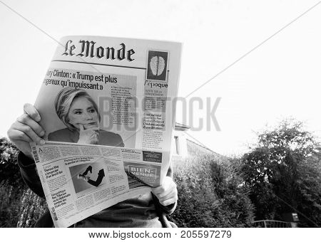 PARIS; FRANCE - SEP 24; 2017: View from below of woman reading latest newspaper Le Monde with portrait of Hillary Clinton on cover about how Donald Trum has lost the moral leadership of United States