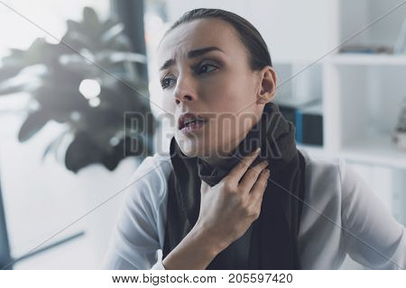 Sick woman sitting at her workplace in the office. She has a sore throat and she wore a scarf. The woman has an unhappy appearance. She suffers from a sore throat