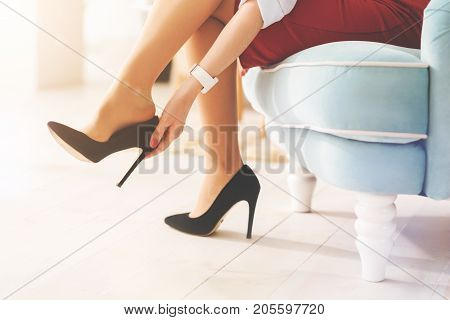 Put it on. Tired office worker sitting in semi position on the armchair and putting right leg on the left one while touching her court shoes