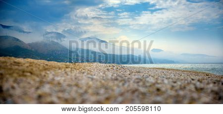 mountains around the beach are shrouded in morning fog