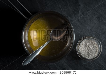 Melted butter in a ladle and a bowl of flour horizontal
